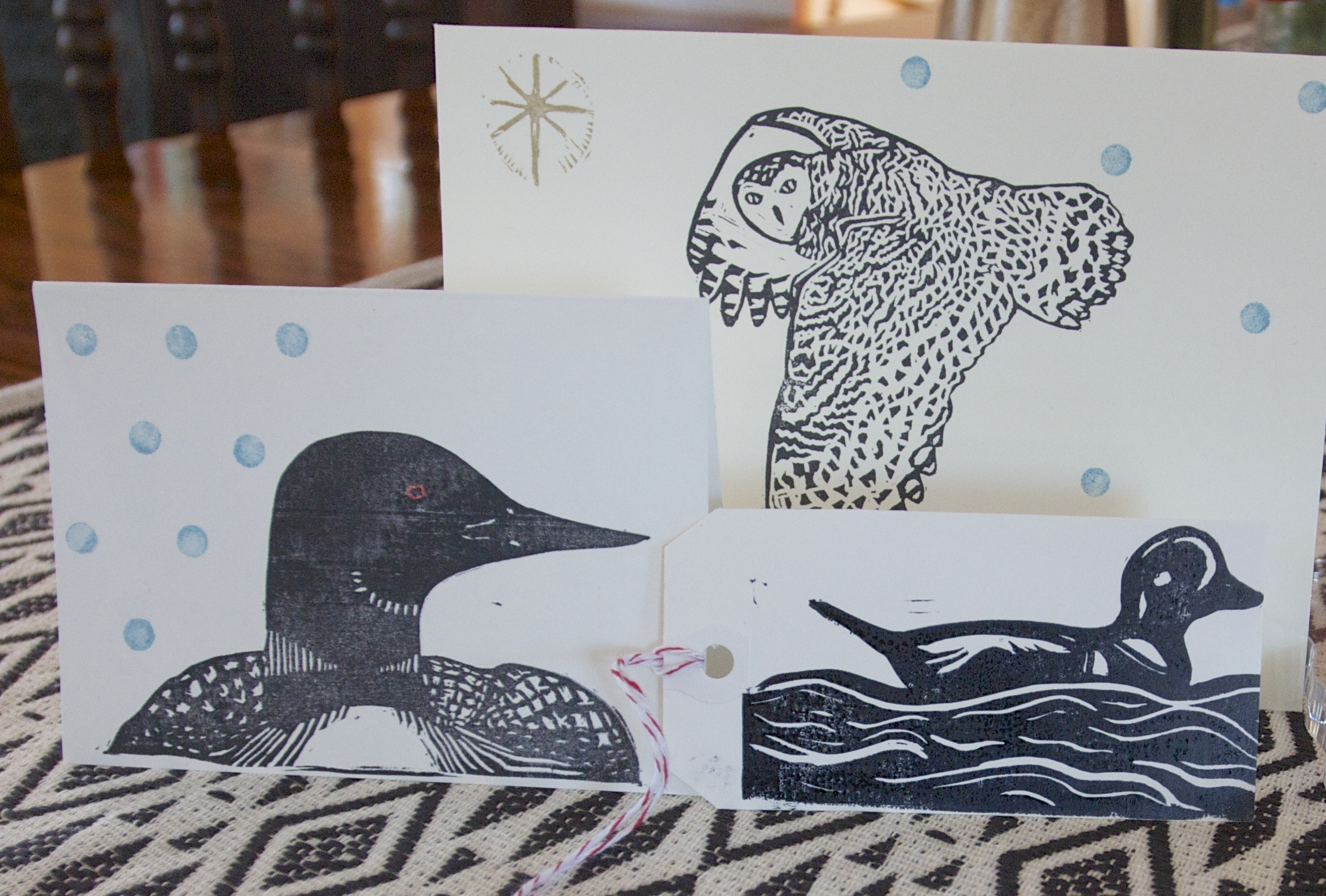 You will receive two Loon cards, and two Snowy Owl cards (all blank on the inside), plus three Harlequin Duck gift tags.  All are hand carved and printed by Mera.