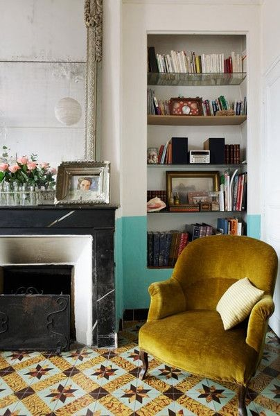 yellow chair in front of color-blocked bookcase